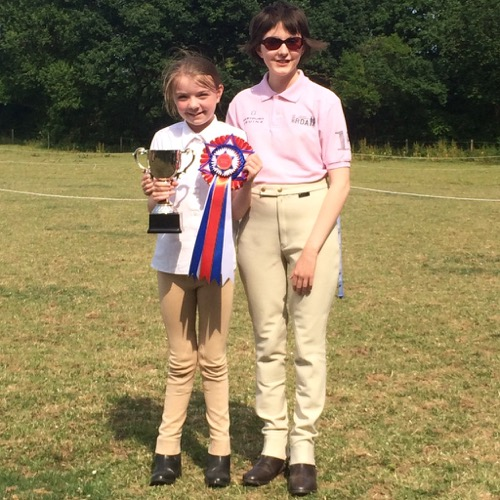 Isabelle holding rosette and trophy with Charlotte