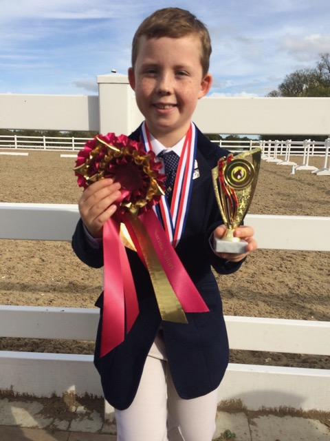 Christopher holding his rosettes and trophy