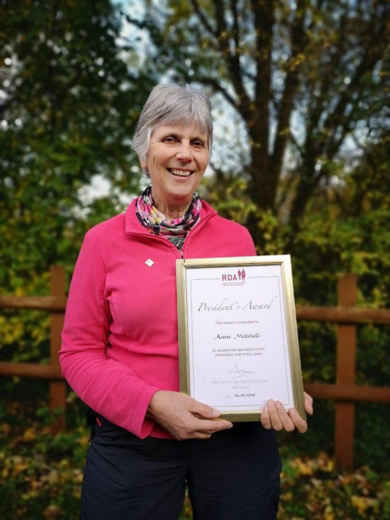 Anne holding her President's Award certificate